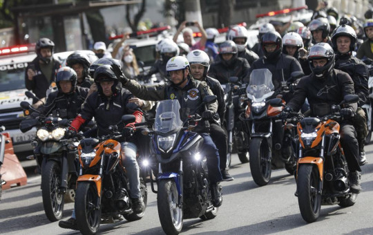 Brazil's President Jair Bolsonaro, center, waves as he leads a caravan of motorcycle enthusiasts following him through the streets of the city, in a show of support for Bolsonaro, in Sao Paulo, Brazil, Saturday, June 12, 2021.