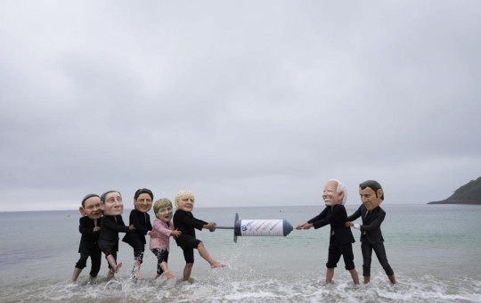 Activists wearing giant heads of the G7 leaders tussle over a giant COVID-19 vaccine syringe during an action of NGO's on Swanpool Beach in Falmouth, Cornwall, England, Friday, June 11, 2021.