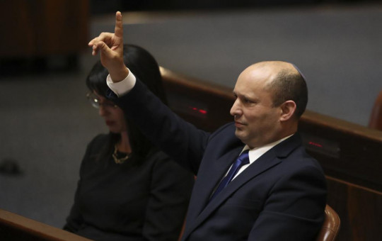 Israel's new prime minister Naftali Bennett raises his hand during a Knesset session in Jerusalem Sunday, June 13, 2021.
