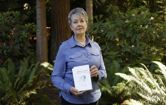 Karen McKnight stands in her backyard on Saturday, June 19, 2021, in Sammamish, Washington, holding two books written by her brother Ross Bagne of Cheyenne, Wyoming.