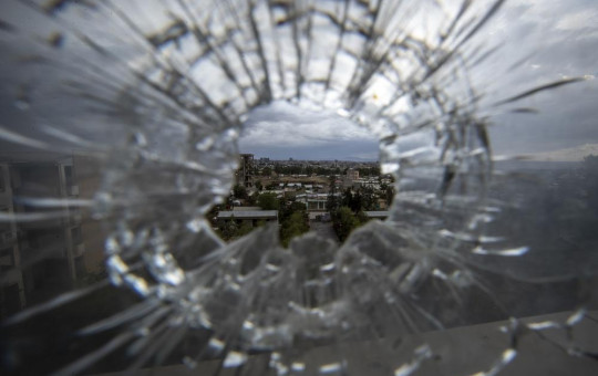 In this Thursday, May 6, 2021 file photo, the city of Mekele is seen through a bullet hole in a stairway window of the Ayder Referral Hospital, in the Tigray region of northern Ethiopia.