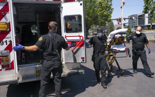 Salem Fire Department paramedics and employees of Falck Northwest ambulances respond to a heat exposure call during a heat wave, Saturday, June 26, 2021, in Salem, Oregon.