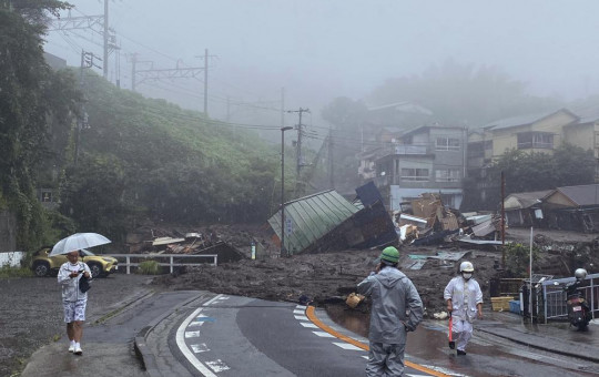 In this photo taken and provided by Satoru Watanabe, a road is covered by mud and debris following heavy rain in Atami city, Shizuoka prefecture, Saturday, July 3, 2021.