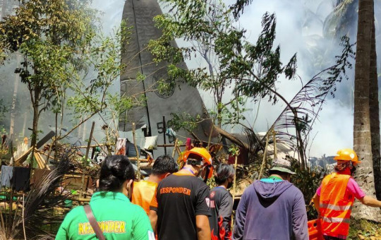 Rescuers search for bodies from the site where a Philippine military C-130 plane crashed in Patikul town, Sulu province, southern Philippines on Sunday, July 4, 2021.