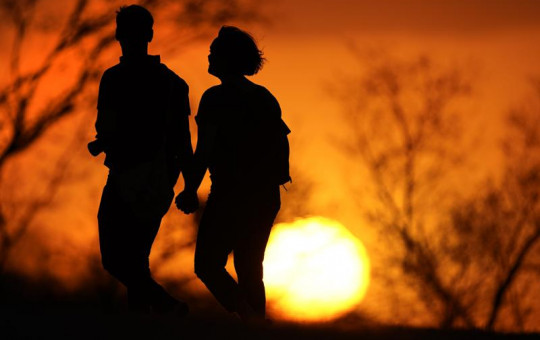 In this Wednesday, March 10, 2021 file photo, a couple walks through a park at sunset in Kansas City, Missouri.