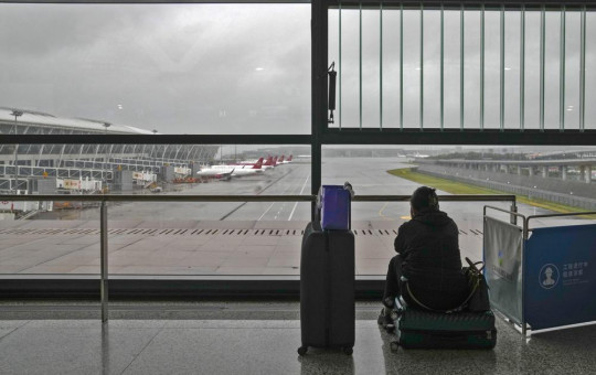 A passenger sits on her luggage watching passenger airplanes parked on the tarmac after all flights were canceled at Pudong International Airport in Shanghai, China, Sunday, July 25, 2021.