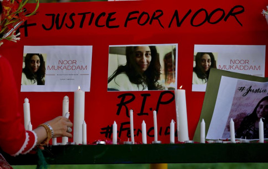 A women's rights activist places a candle beside a poster with the pictures of Noor Mukadam, who was recently beheaded, during a candle light vigil to pay tribute to Noor and other domestic violence victims, in Islamabad.