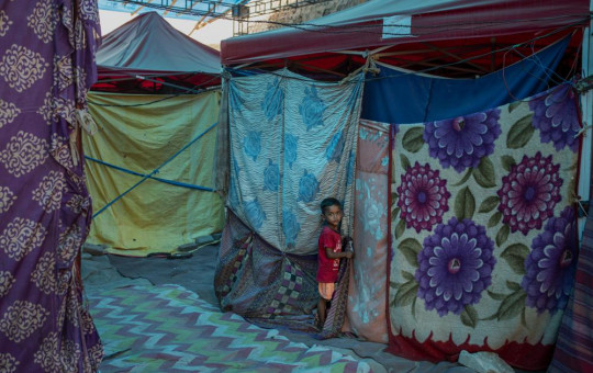 A young Rohingya refugee boy stands outside a tent at a refugee camp alongside the banks of the Yamuna River in the southeastern borders of New Delhi, sprawling Indian capital, July 1, 2021.