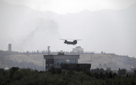 A US Chinook helicopter flies over the U.S. Embassy in Kabul, Afghanistan, Sunday, Aug. 15, 2021.