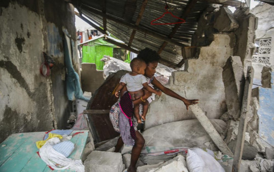 A woman carries her child as she walks in the remains of her home destroyed by Saturday´s 7.2 magnitude earthquake in Les Cayes, Haiti, Sunday, Aug. 15, 2021.