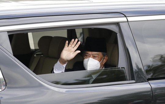 Embattled Malaysian Prime Minister Muhyiddin Yassin waves from a car while entering the National Palace to meet with the King in Kuala Lumpur, Malaysia, Monday, Aug. 16, 2021.