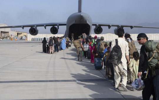 U.S. Air Force loadmasters and pilots assigned to the 816th Expeditionary Airlift Squadron, load people being evacuated from Afghanistan onto a U.S. Air Force C-17 Globemaster III at Hamid Karzai International Airport in Kabul on Tuesday.