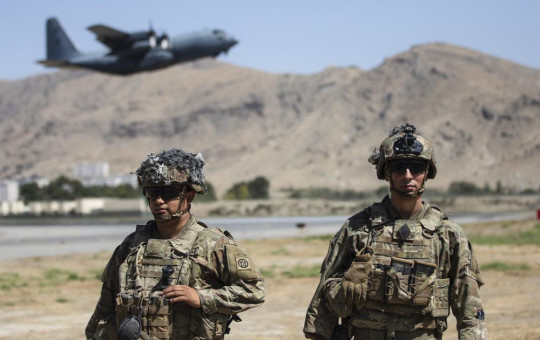 In this image provided by the Department of Defense, two paratroopers assigned to the 1st Brigade Combat Team, 82nd Airborne Division conduct security while a C-130 Hercules takes off during a evacuation operation in Kabul, Afghanistan, Wednesday.