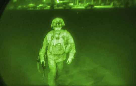 In this image made through a night vision scope and provided by U.S. Central Command, XVIII Airborne Corps, boards a C-17 cargo plane at the Hamid Karzai International Airport in Kabul, Afghanistan, Monday.